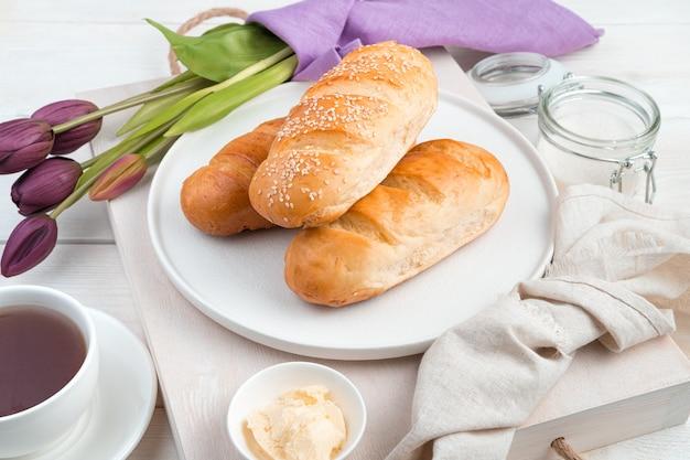 Булочки на праздничном фоне с чаем и цветами. вид сбоку. концепция праздничных кулинарных фонов 8 марта. Premium Фотографии