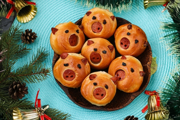 Buns pigs stuffed with sausage on blue background, top view, idea for the new year and children's holiday