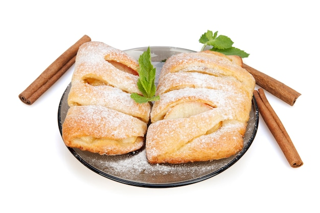 白の皿に粉砂糖をまぶしたリンゴ、シナモン、ミントのパン
