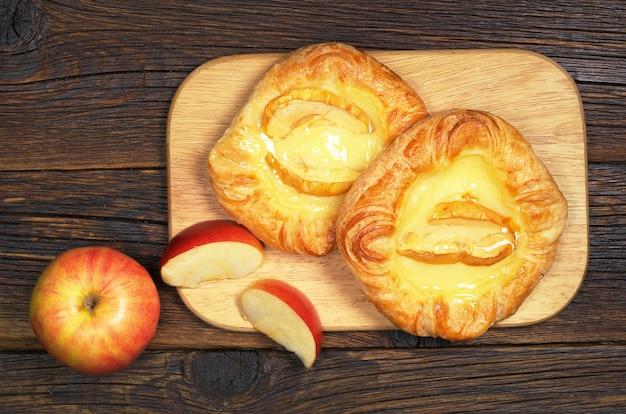 暗い木製のテーブル、上面図のまな板にリンゴとパン