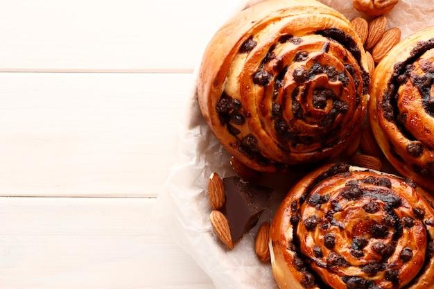 갈색 나무 바탕에 계피와 초콜릿을 넣은 빵. 시나몬 스틱과 블랙 에스프레소 커피. 텍스트에 대 한 장소입니다. 평면도.