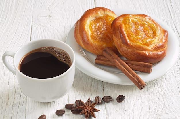 白い木製の背景にジャムとホットコーヒーのカップとパン