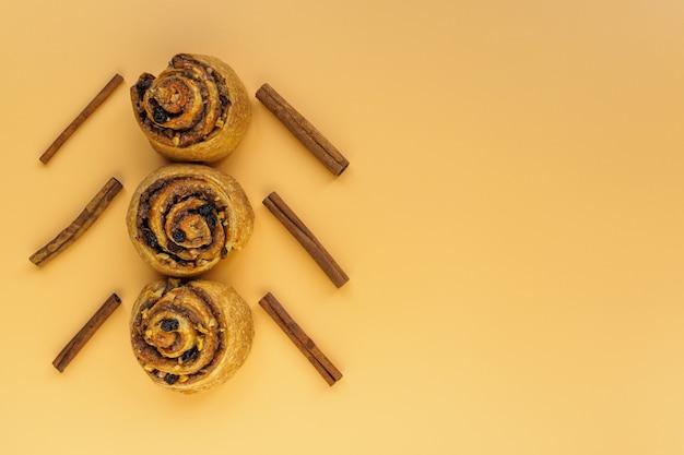 Булочки с орехами, изюмом и корицей в виде елки на оранжевом фоне