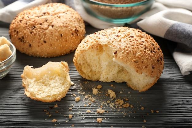 Булочки с кунжутом и хлебом на деревянном столе