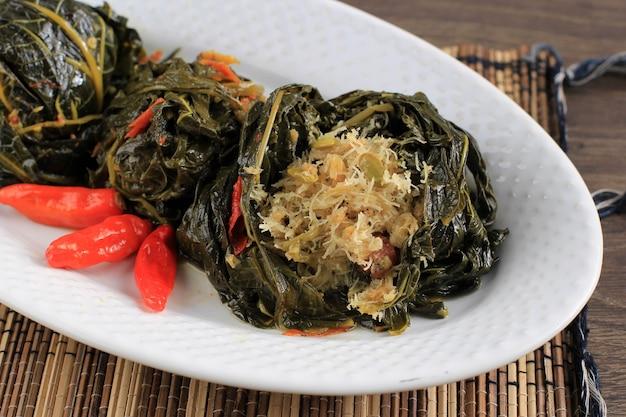 Бунтил - это традиционная индонезийская еда, приготовленная из листьев папайи / маниока, фаршированных тертым кокосом, петай-циной и анчоусами. популярный в яванской и суданской кухне, копия пространства изолирована