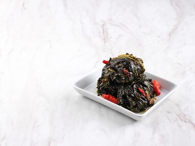 Бунтил - это традиционная индонезийская еда, приготовленная из листьев папайи / маниока, фаршированных тертым кокосом, петай-циной и анчоусами. популярно в яванской и суданской кухне, copy space