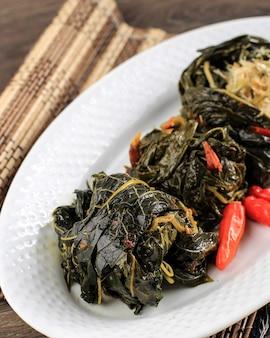 Бунтил - это традиционная индонезийская еда, приготовленная из листьев папайи / маниока, фаршированных тертым кокосом, петай-циной и анчоусами. популярно в яванской и суданской кухне