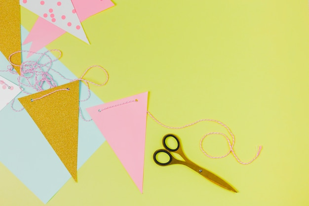 Bunting paper and scissor on green background