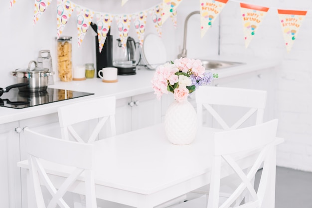 Bunting over table with beautiful flower vase in modern kitchen