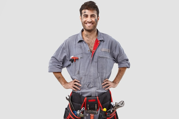 Buoyant successful handyman posing against the white wall