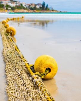남아프리카 케이프 타운의 젖은 모래 해안에서 바다로 뻗어있는 로프에 부표