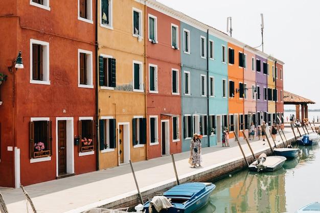 Бурано, венеция, италия - 2 июля 2018: панорамный вид на ярко окрашенные дома и водный канал с лодками в бурано, это остров в венецианской лагуне. люди ходят и отдыхают на улицах