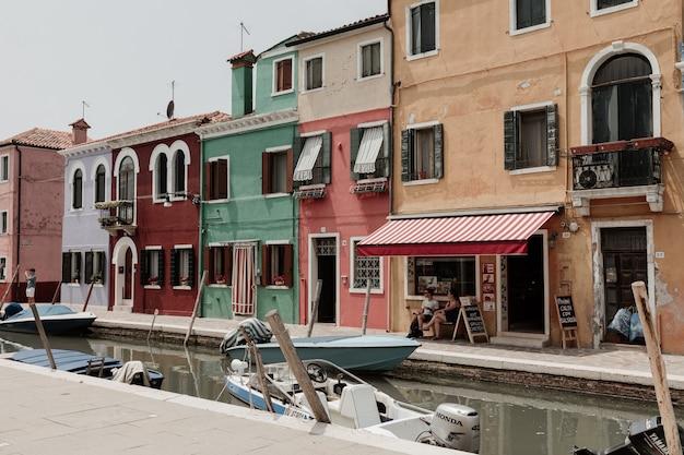 부라노, 베니스, 이탈리아 - 2018년 7월 2일: 부라노(burano)에 보트가 있는 밝은 색상의 주택과 수로의 탁 트인 전망은 베네치아 석호(venetian lagoon)에 있는 섬입니다. 사람들은 거리에서 걷고 휴식을 취한다.