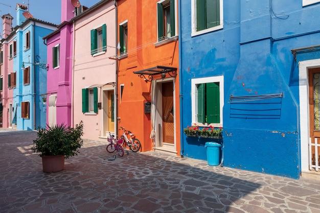 Бурано, венеция, италия - 2 июля 2018: панорамный вид на ярко окрашенные дома бурано - остров в венецианской лагуне. люди ходят и отдыхают на улицах. летний солнечный день и голубое небо