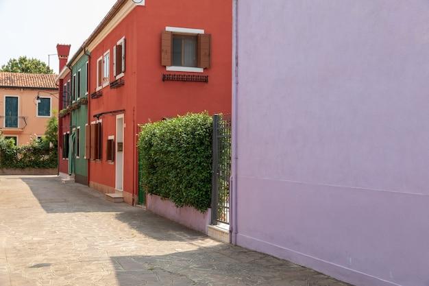 부라노, 베니스, 이탈리아 - 2018년 7월 2일:부라노의 밝은 색 주택의 탁 트인 전망은 베네치아 석호에 있는 섬입니다. 사람들은 거리를 걷고 휴식을 취합니다. 여름 화창한 날과 푸른 하늘