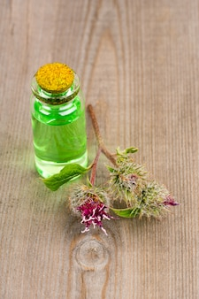 Burdock essential oil for spa or massage, vertical image