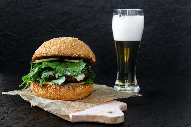 Бургер и пиво в стакане на темном фоне. гамбургер