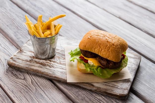 버거와 감자 튀김의 양동이입니다. 종이 조각에 햄버거입니다. 맛있는 패스트 푸드 식사. 쇠고기 버거의 전통적인 조리법.