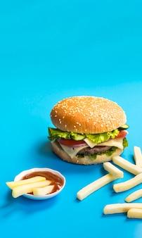 파란색 배경에 햄버거와 감자 튀김 무료 사진