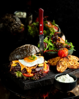 Burger in black bread bun with fried egg.