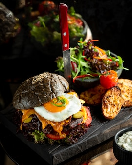 Burger in black bun with fried egg and potatoes.