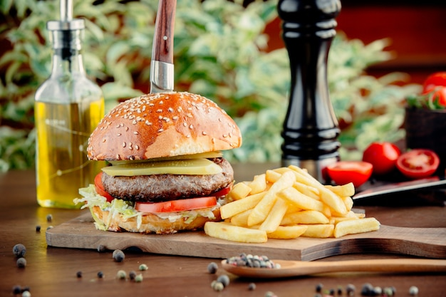 Burger in bread bun with meat and french fries.
