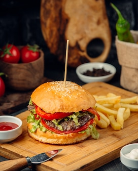 Burger in bread bun with potatoes on a wooden board.