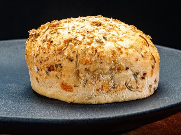 素朴な石にゴマとオレガノとパルメザンチーズを添えたハンバーガーパン。
