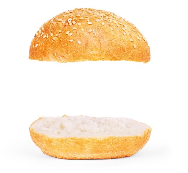 버거 롤빵은 비어 있습니다. 흰색 배경에 분리된 참깨를 넣은 미국 음식 클래식 버거 라운드 롤빵. 재료가 들어가지 않은 버거빵. 구운 구운 햄버거 롤빵 레이어가 흰색으로 날아갑니다.