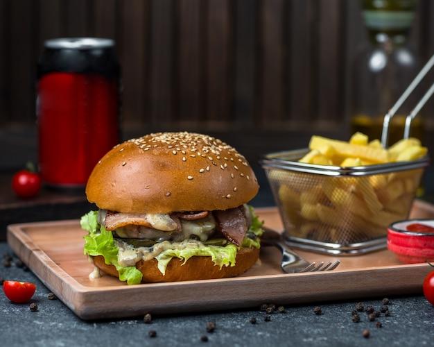 Булочка с начинкой из бургера, фаршированная мясом и овощами, подается в подносе с картофелем.
