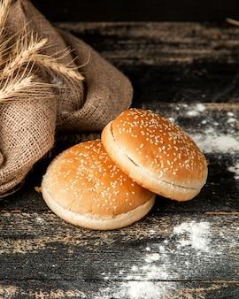 Булочки с гамбургером с кунжутом, пшеницей и мукой на столе