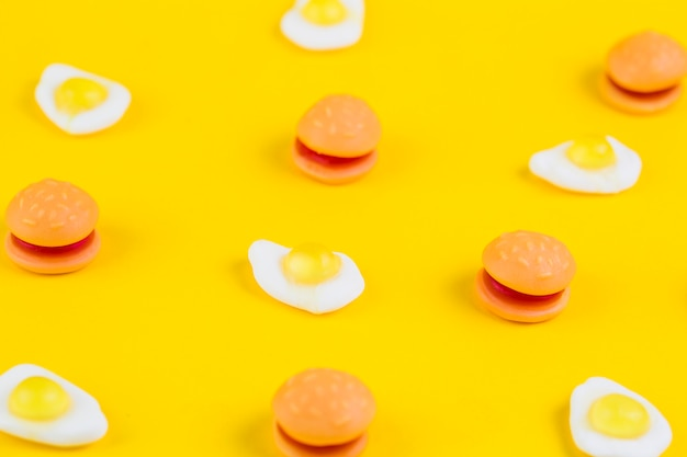Burger candies and fried egg gummies on yellow surface