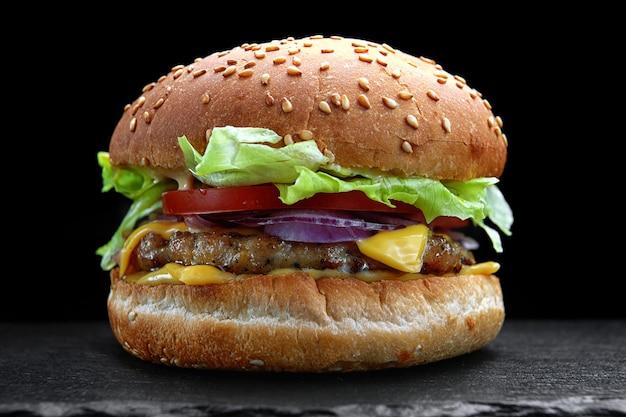 Бургер, чизбургер, гамбургер с мясной котлетой, сыром, листьями салата и помидорами