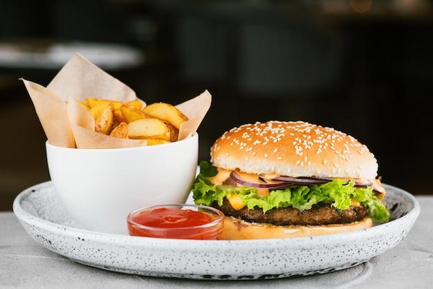 콘크리트 테이블, 레스토랑 배경에 샐러드와 소스를 곁들인 버거 클로즈업. 감자 튀김과 케첩을 곁들인 큰 버거.