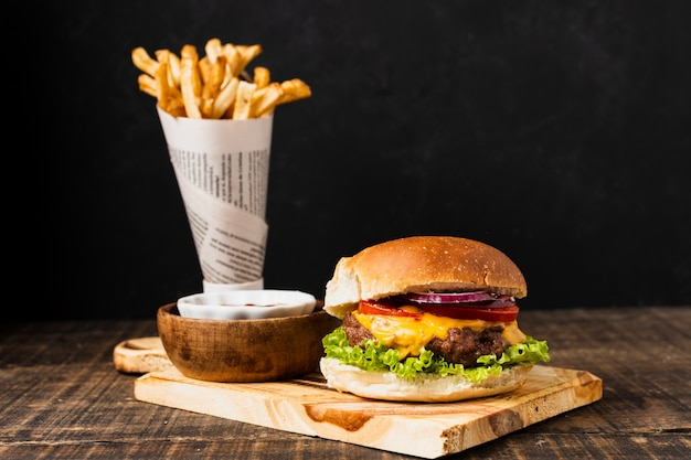 Burger on cutboard with french fries