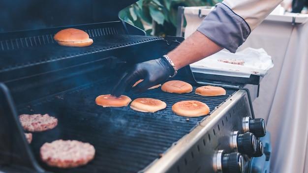 Котлета бургер и булочка на гриле, пикник с шашлыком на свежем воздухе.