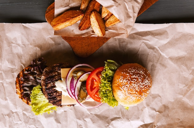 Burger decomposed into its components on kraft paper on a wooden table. package of chips.