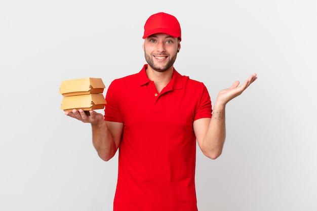 Мужчина с доставкой бургеров чувствует себя счастливым и удивляется чему-то невероятному