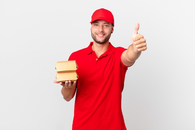 Бургер доставить мужчина чувствует себя гордым, позитивно улыбается, показывает палец вверх