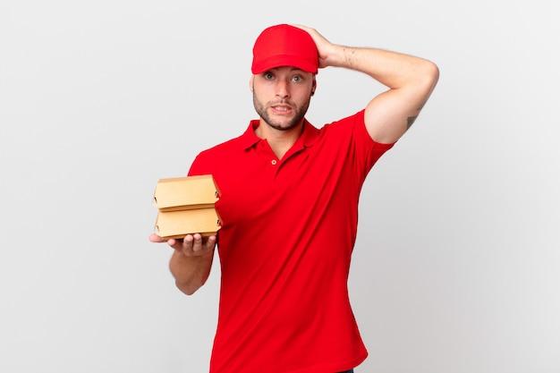 Бургер доставить мужчине, чувствуя стресс, беспокойство или испуг, с руками за голову