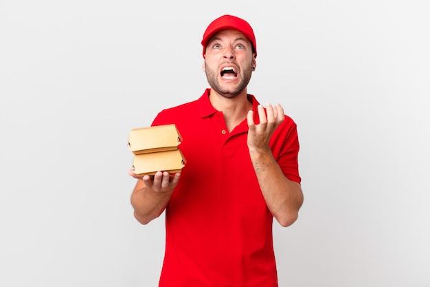 Мужчина с доставкой бургеров выглядит отчаявшимся, расстроенным и подчеркнутым