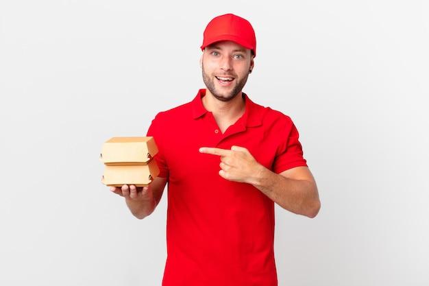Человек доставки бургеров выглядит взволнованным и удивленным, указывая в сторону