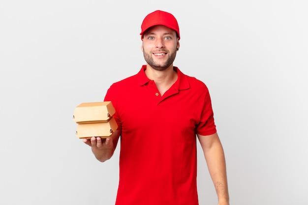 Мужчина с доставкой бургеров выглядит счастливым и приятно удивленным