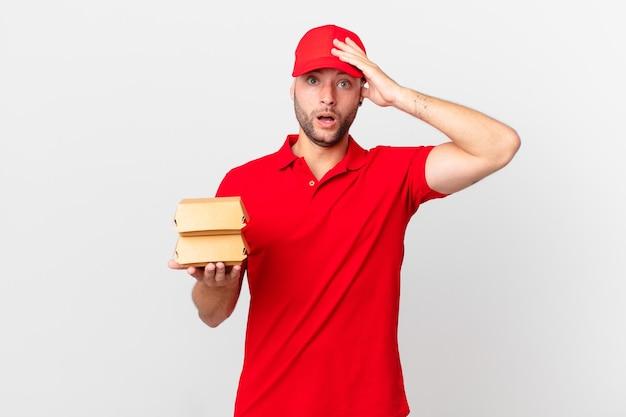Доставщик бургеров мужчина выглядит счастливым, удивленным и удивленным