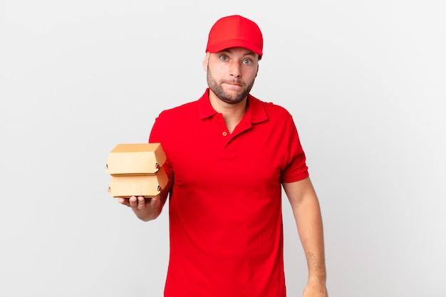 Человек-доставщик бургеров выглядит озадаченным и сбитым с толку