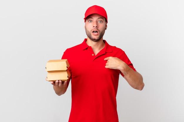 Мужчина-доставщик бургеров выглядит шокированным и удивленным с широко открытым ртом, указывая на себя