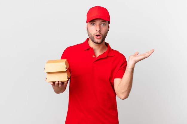 Доставщик бургеров выглядит удивленным и шокированным, с отвисшей челюстью держит предмет