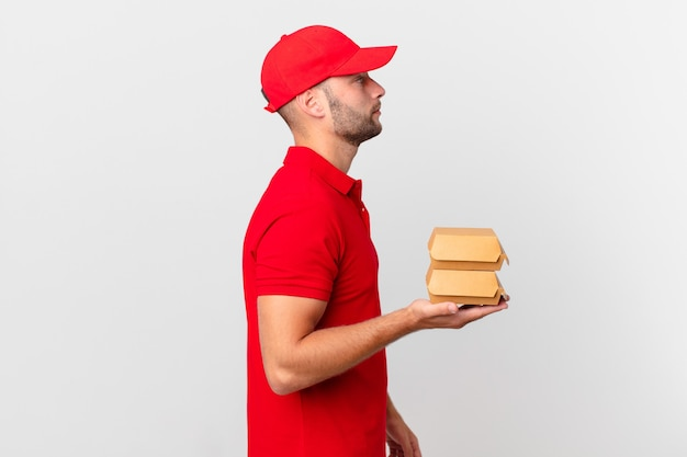 Burger deliver man on profile view thinking, imagining or daydreaming