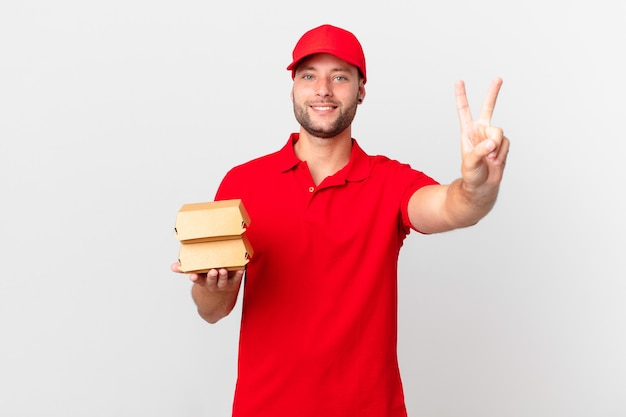 Доставщик бургеров улыбается и выглядит дружелюбно, показывая номер два