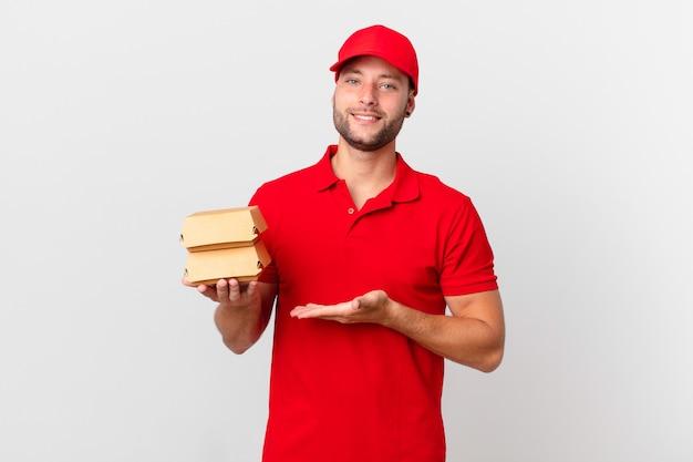 Бургер доставить человека, весело улыбаясь, чувствуя себя счастливым и показывая концепцию